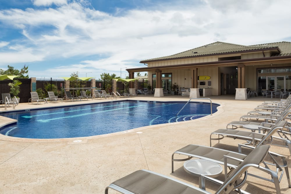 Beautiful swimming pool area with plenty of seating nearby at Kapolei Lofts in Kapolei, HI