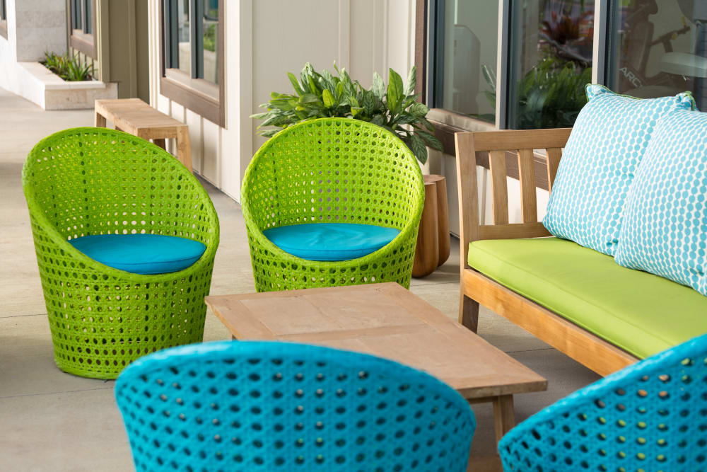 Colorful and comfortable seating in the shade near the poolside cabana at Kapolei Lofts in Kapolei, HI