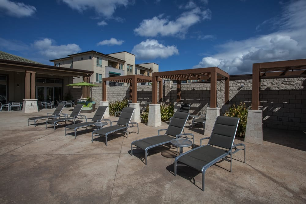 Comfortable seating areas to work on your tan near the pool at Kapolei Lofts in Kapolei, HI