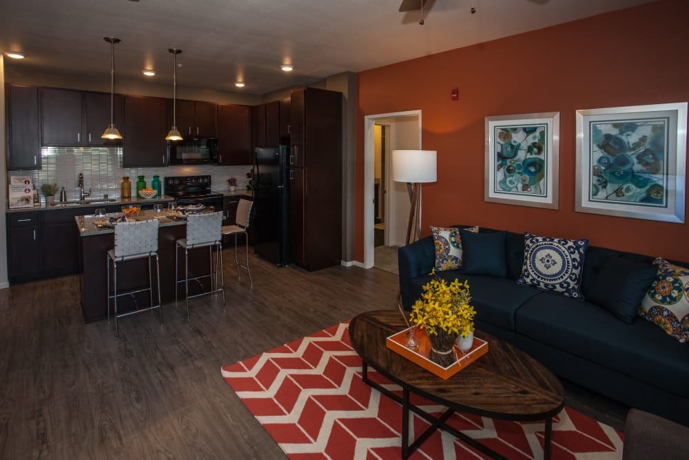 Open-concept floor plan with hardwood floors and custom lighting in model apartment home at Kapolei Lofts in Kapolei, HI