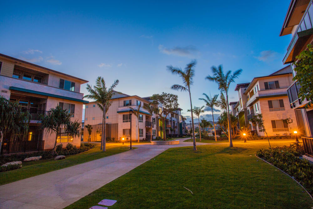 Evening view of well-lit exterior common areas at Kapolei Lofts in Kapolei, HI