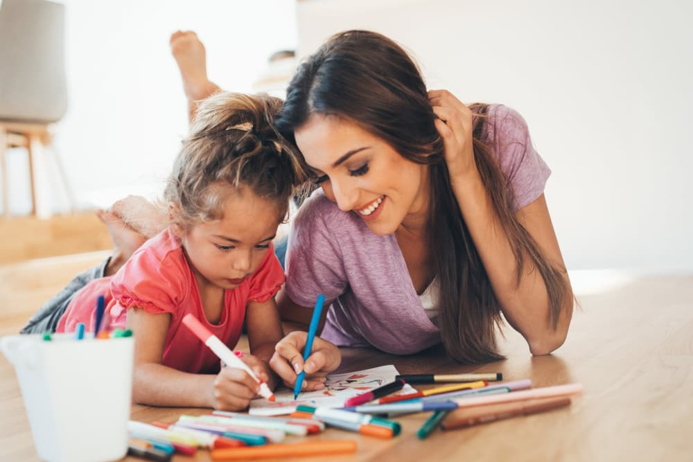Mother teaching her daughter to draw at E Street Apartments in Sacramento, California