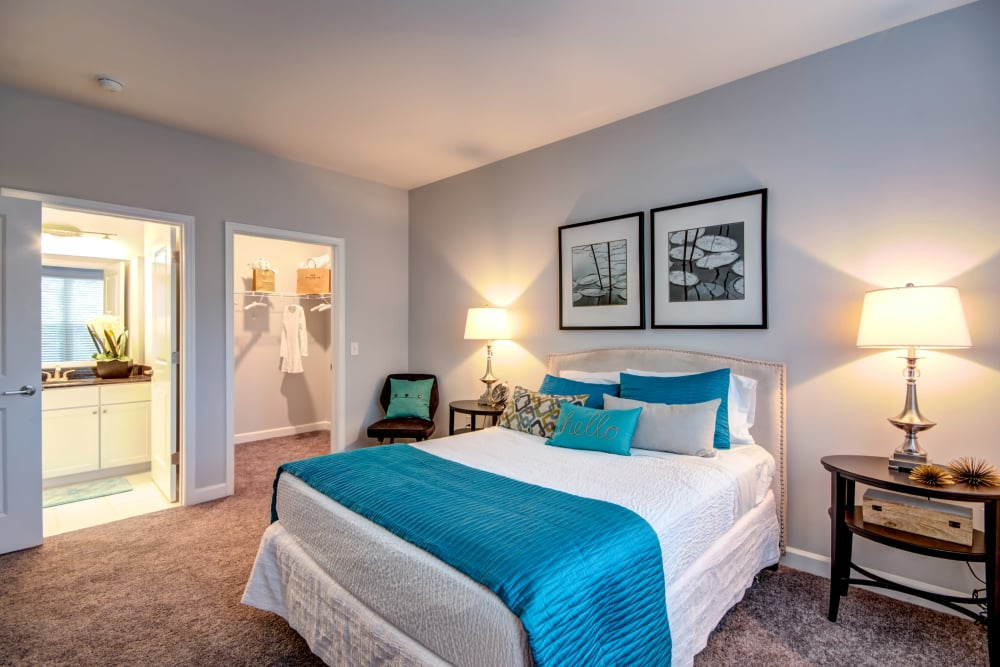 Bedroom model with blue accents at Manassas Station Apartments in Manassas, Virginia