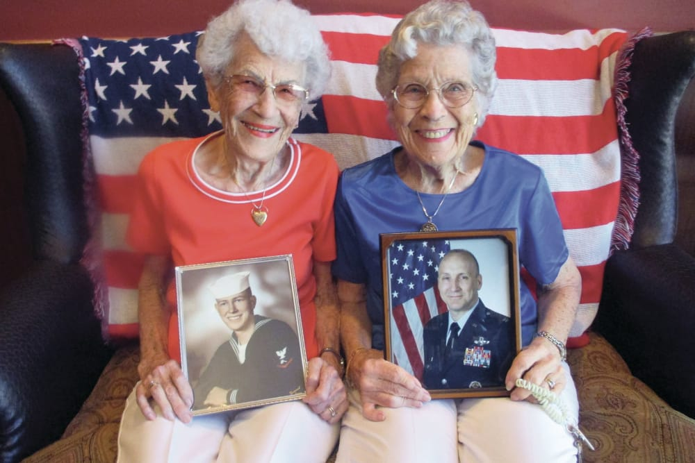 Two senior women holding images of loved ones at Hawthorn Senior Living in Vancouver, Washington