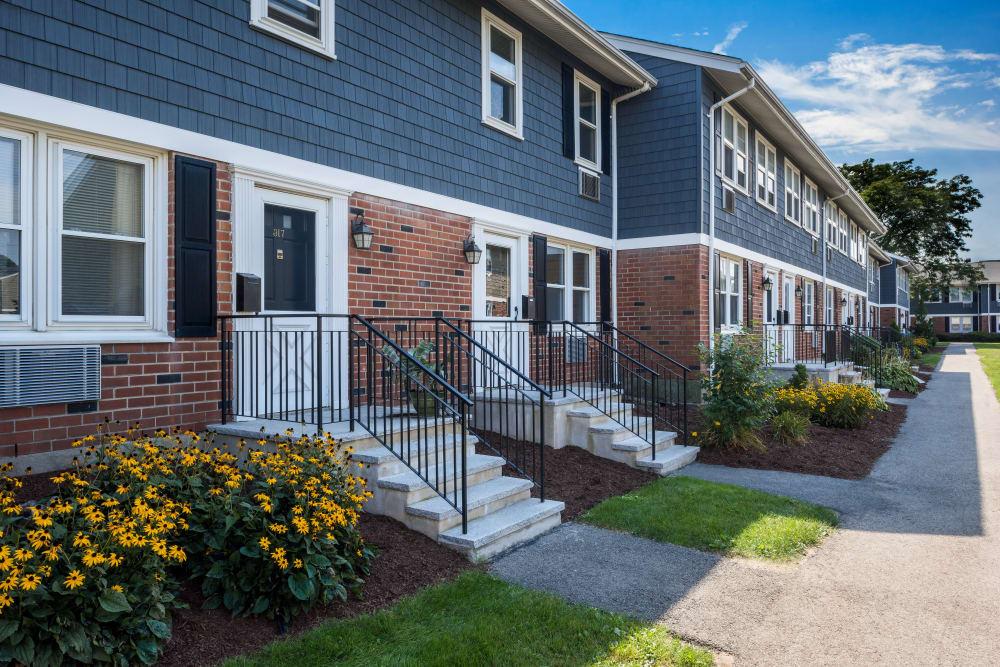 Flowers and green grass outside resident buildings at Brandywyne Village in East Boston, Massachusetts