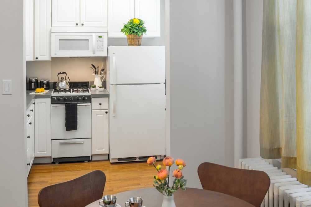 Kitchen featuring white appliances at Burbank Apartments in Boston, Massachusetts