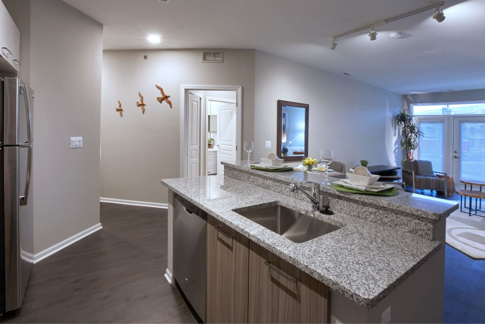 Open-concept floor plan showcasing modern kitchen with island and hardwood floors in model home at Five Points in Auburn Hills, Michigan