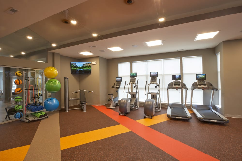 Cardio machines, exercise balls, and flatscreen TV in the fitness center at Five Points in Auburn Hills, Michigan