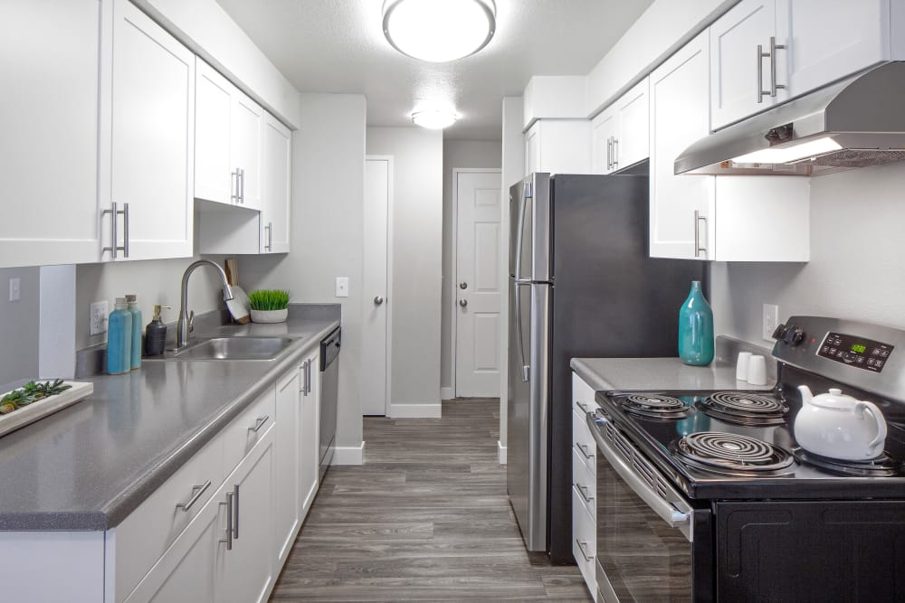 Modern kitchen with granite countertops and hardwood-style floors in model home at Heatherbrae Commons in Milwaukie, Oregon