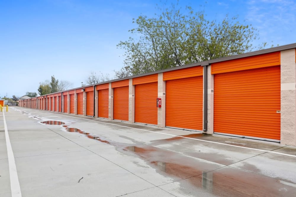 Row of outdoor storage units with orange roll up doors at A-1 Self Storage in San Jose, California