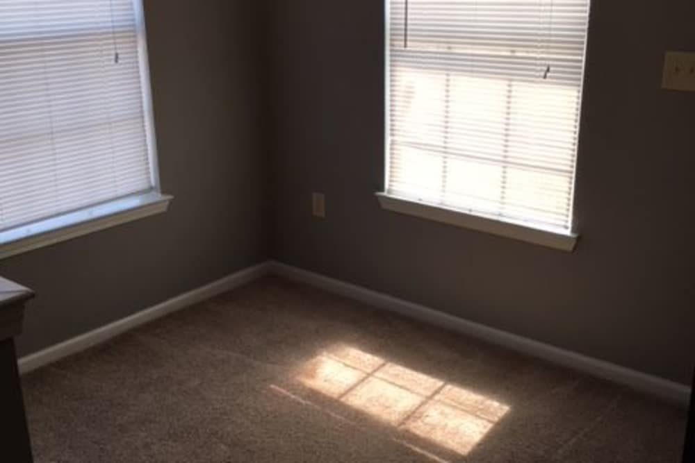 Bedroom with two windows at Harbin Pointe Apartments in Bentonville, Arkansas