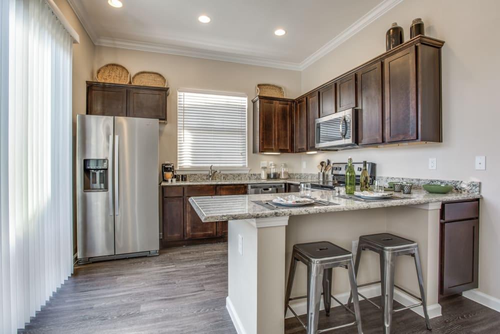 Kitchen and breakfast bar at Avilla Northside in McKinney, Texas