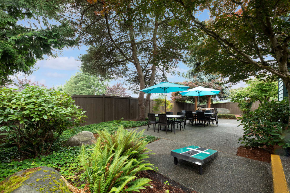 common area courtyard with corn hole boards, lush landscaping, and chairs and umbrellas