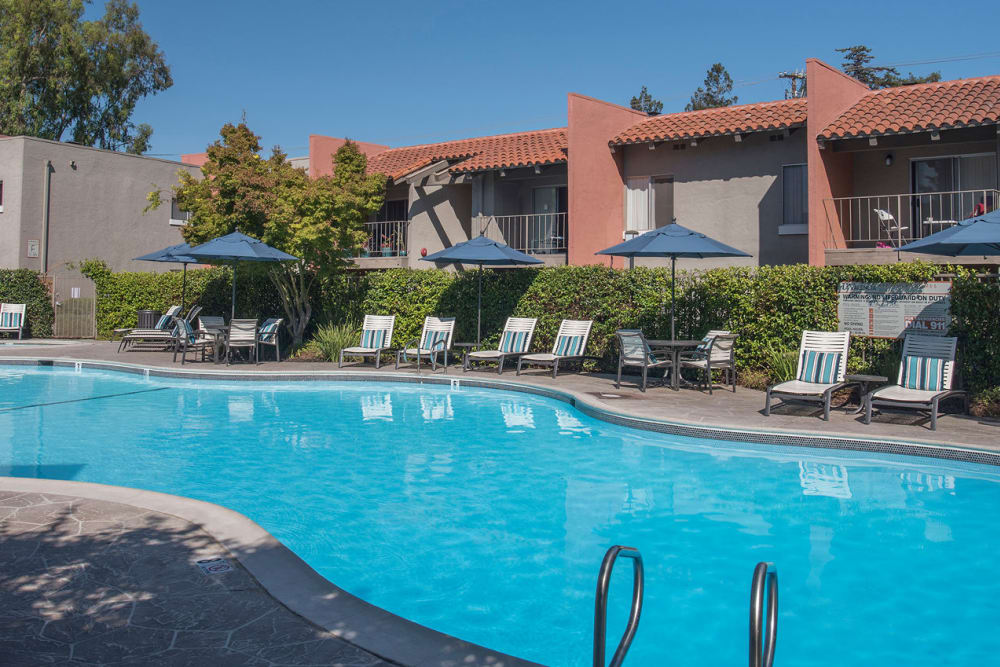 Large swimming pool with a sundeck at La Valencia Apartment Homes in Campbell, California