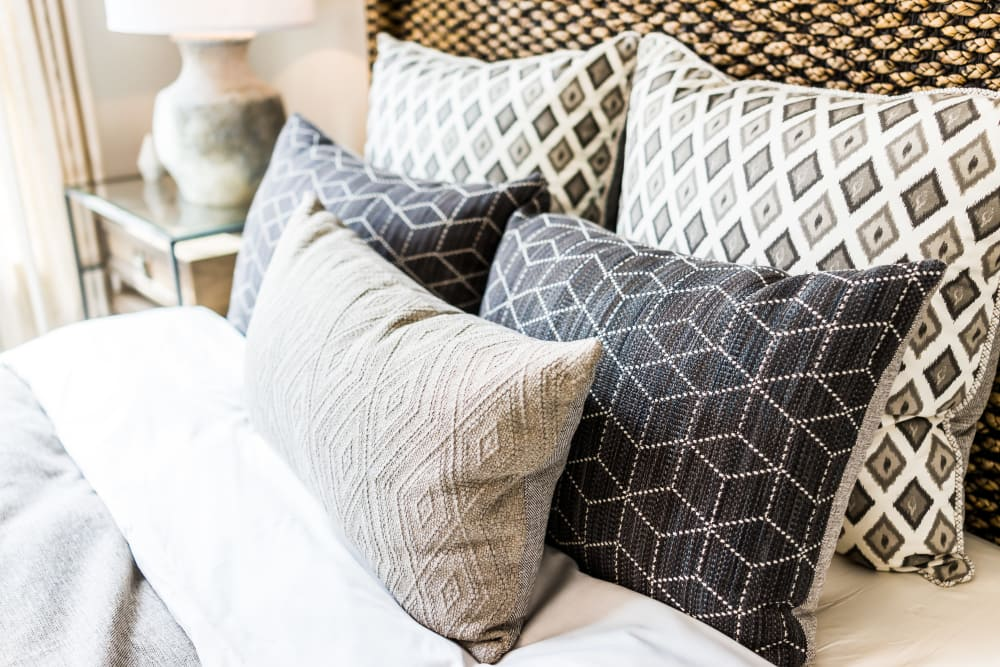 Bed with decorative pillows in model home bedroom at Cooper Creek in Louisville, Kentucky