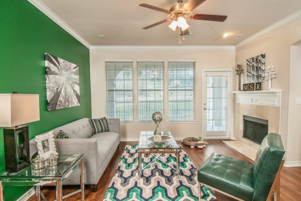 Cozy living room with accent wall and ceiling fan in model home at Meritage at Steiner Ranch in Austin, Texas