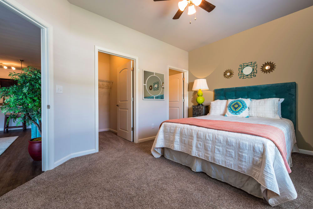 Spacious bedroom with ceiling fan and walk-in closet in model home at Valley Farms in Louisville, Kentucky
