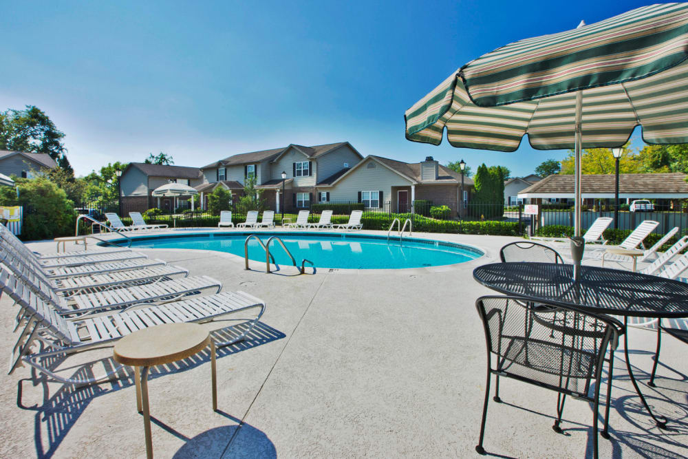 Beautiful swimming pool surrounded by chaise lounges and shaded seating at Cooper Creek in Louisville, Kentucky