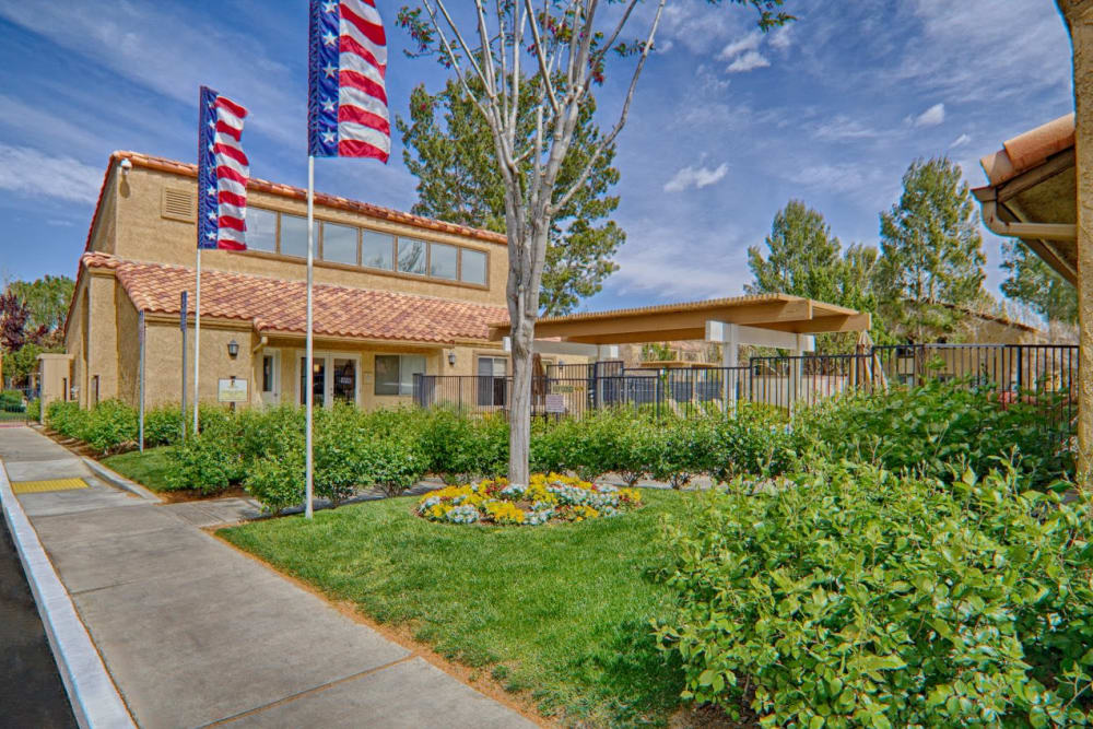 Flags and landscaping in front of leasing office at Granada Villas Apartment Homes in Lancaster, California