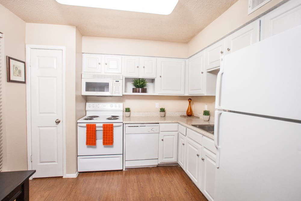 Kitchen with hardwood floors and white appliances in model home at Ashley Oaks in San Antonio, Texas