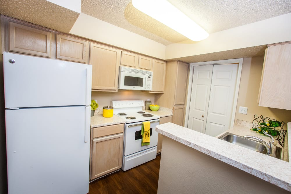 Light wood cabinetry and white appliances in model home's kitchen at Ashley Oaks in San Antonio, Texas
