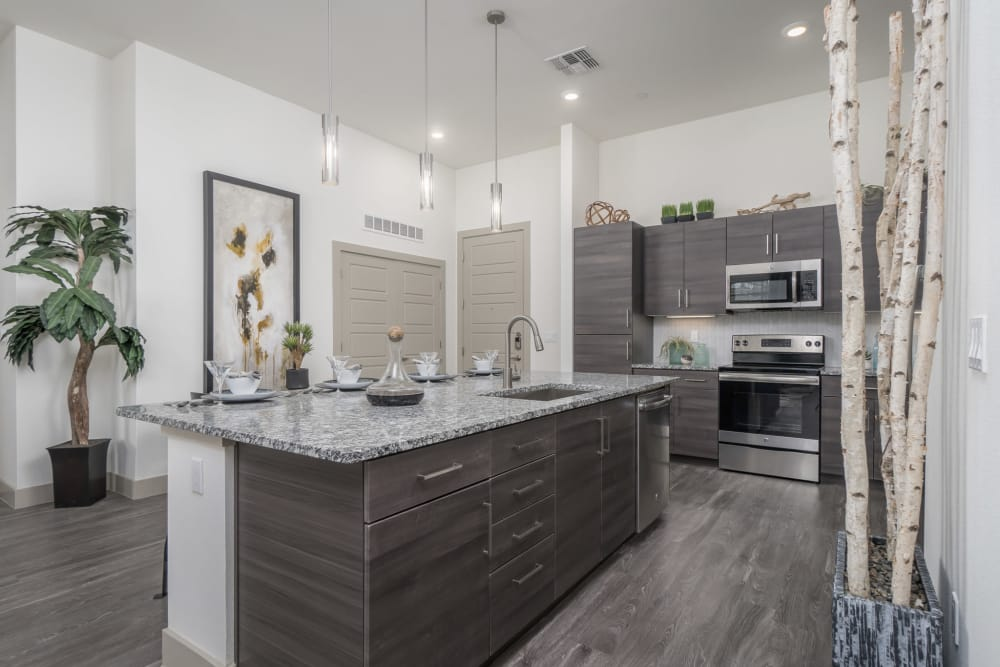The island in this apartment kitchen has plenty of drawers for storage at The District at Scottsdale in Scottsdale, Arizona