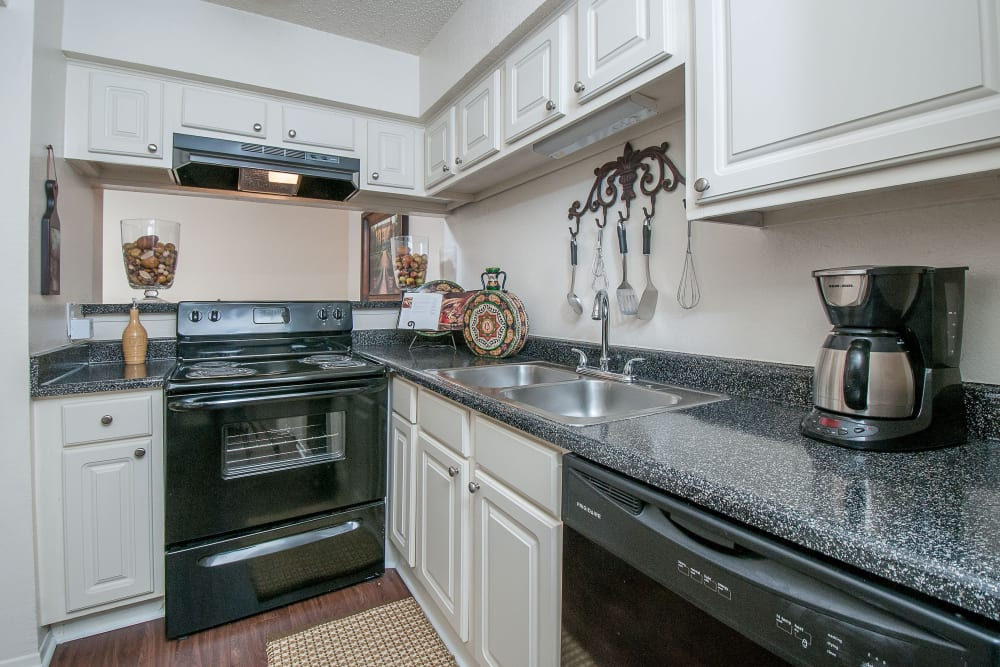 White cabinetry and black appliances in model home's kitchen at Grayson Ridge in North Richland Hills, Texas