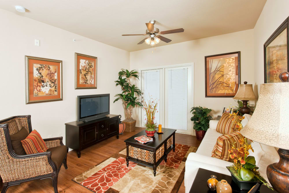 Well-decorated living area with hardwood floors and ceiling fan in model home at The Hills at Fair Oaks in Fair Oaks Ranch, Texas