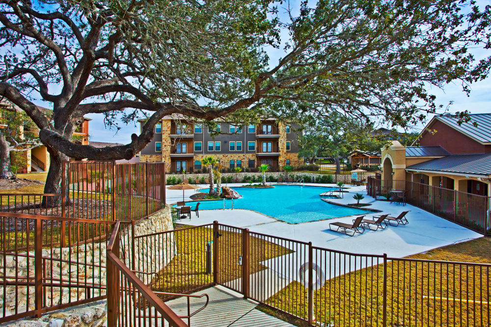 View of swimming pool area from pathway at The Hills at Fair Oaks in Fair Oaks Ranch, Texas