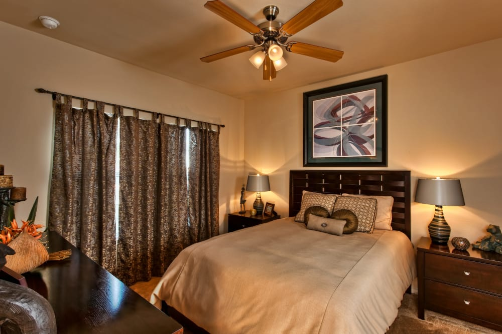 Master bedroom with luxurious drapes and ceiling fan in model home at Springmarc Apartments in San Marcos, Texas