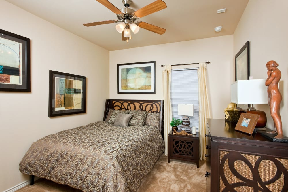 Guest bedroom with ceiling fan in model home at Springmarc Apartments in San Marcos, Texas