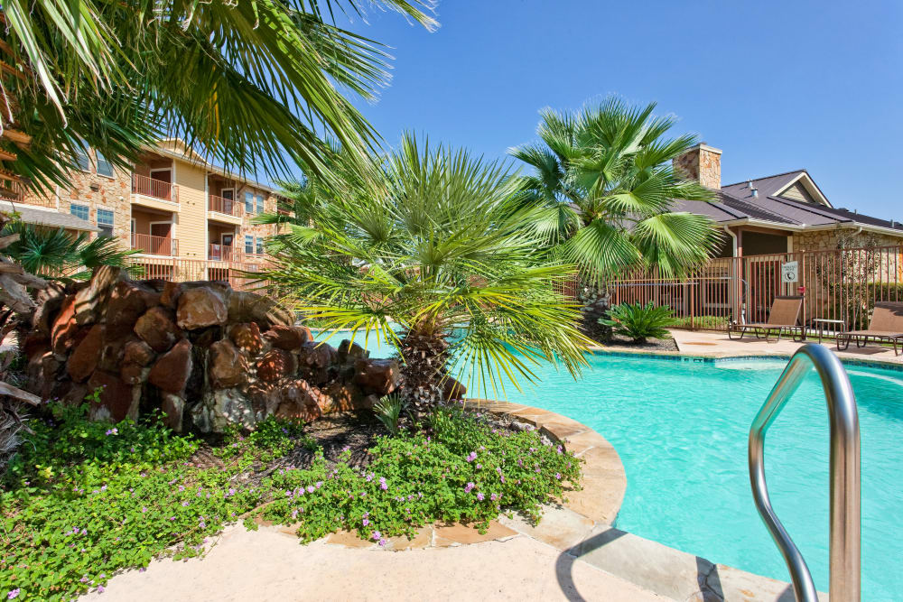 Beautiful swimming pool area on a sunny day at Springmarc Apartments in San Marcos, Texas