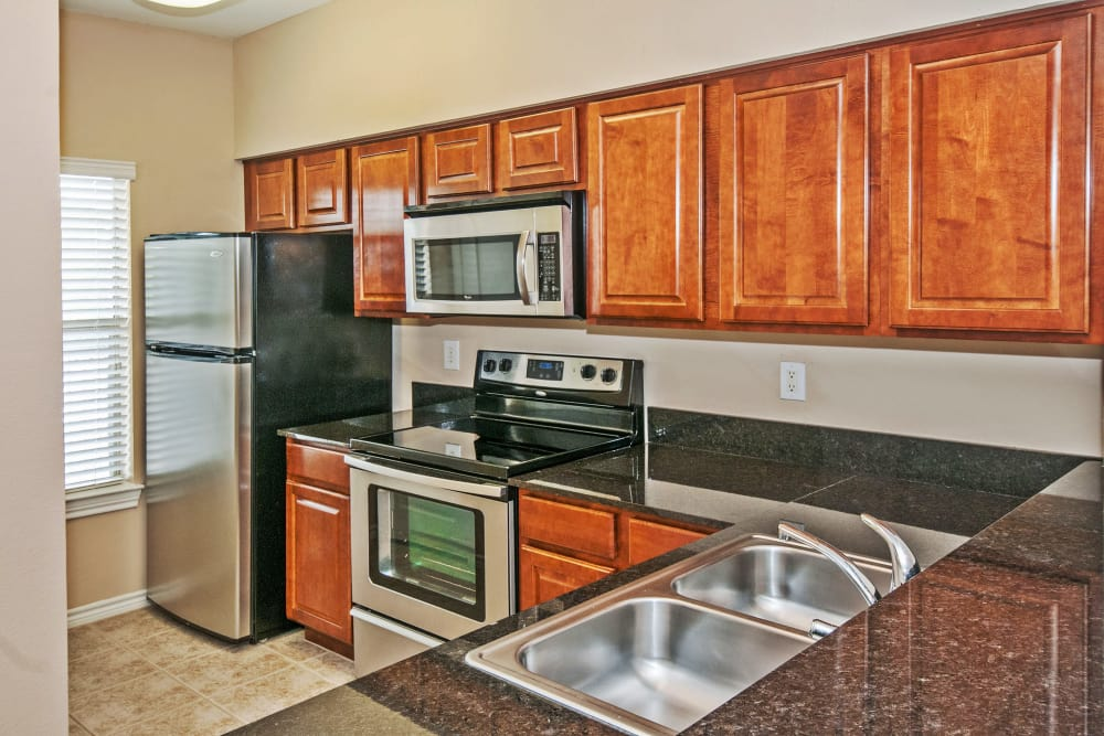 Cherry Wood Cabinetry And Stainless Steel Appliances In Model Homeu0027s  Kitchen At Rosemont At Olmos