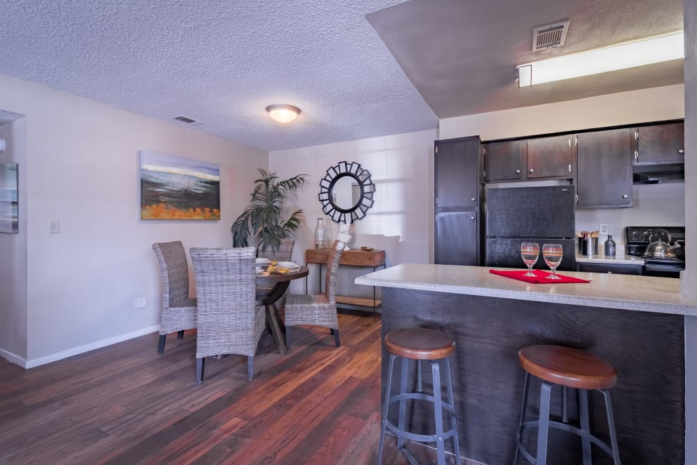 Dining room and kitchen with a breakfast bar at Presidio Apartments in Allen, Texas