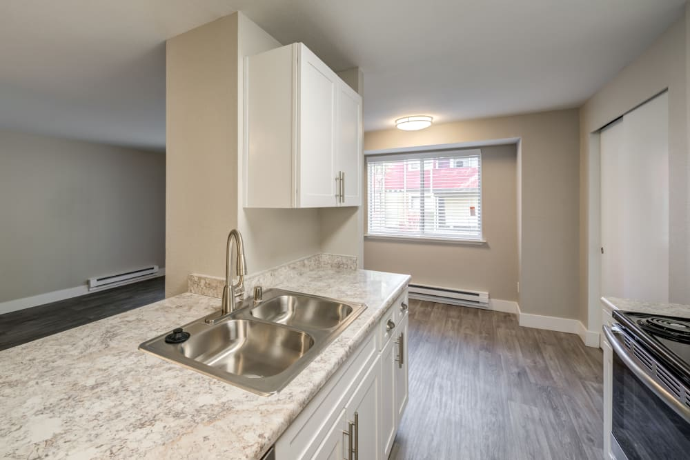 Black appliances and modern conveniences in Chestnut Hills Apartments model apartment home's kitchen