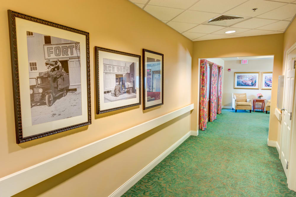 Hallway with pictures at The Lynmoore at Lawnwood Assisted Living and Memory Care in Fort Pierce, Florida.