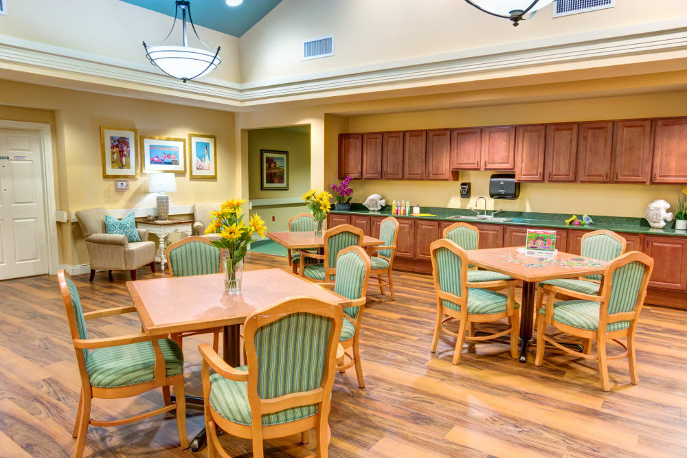 Resident Dining area with kitchen at The Lynmoore at Lawnwood Assisted Living and Memory Care in Fort Pierce, Florida.
