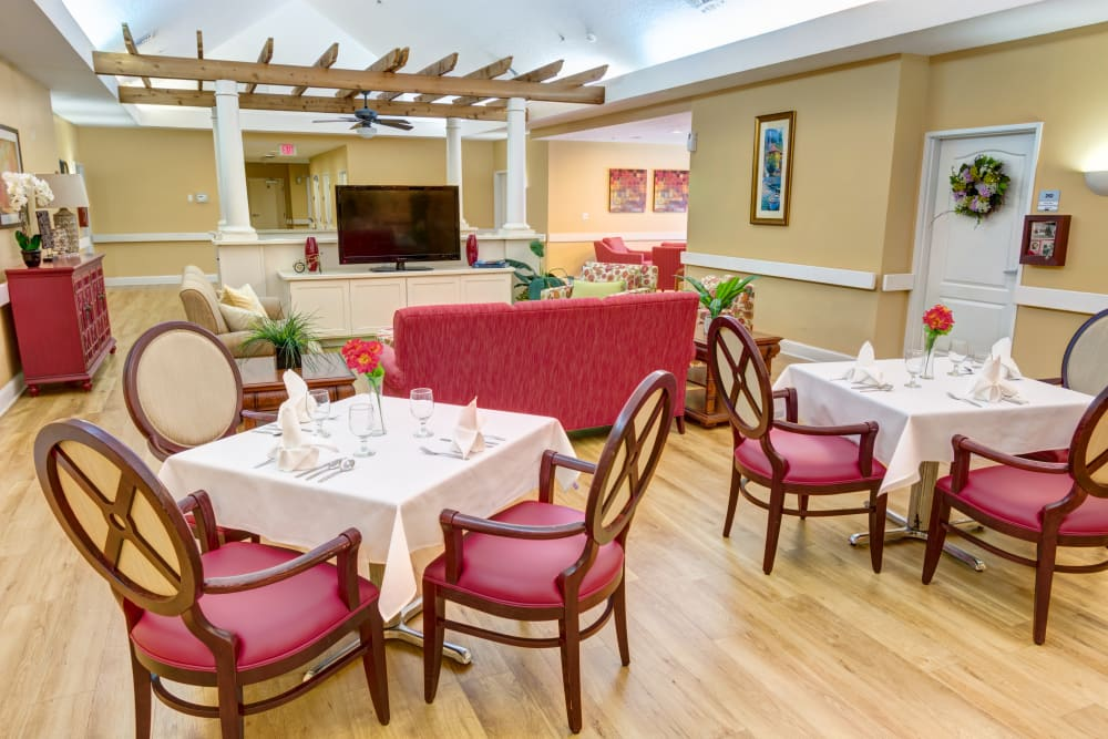Dining area with a TV at The Lynmoore at Lawnwood Assisted Living and Memory Care in Fort Pierce, Florida.