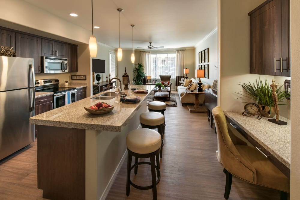 Gourmet kitchen with granite countertops and adjacent workspace in model home at San Travesia in Scottsdale, Arizona