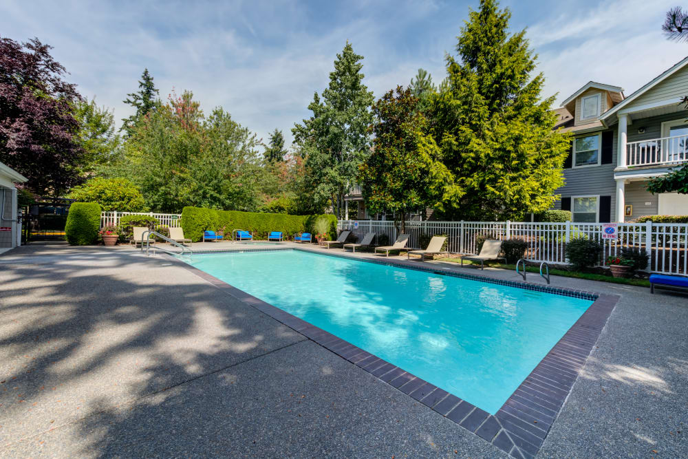 Swimming pool and lounge seating at Bradley Park Apartments in Puyallup, Washington