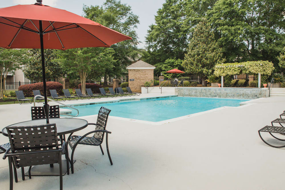 Poolside chairs with umbrella at Brighton Park Apartments in Byron, Georgia