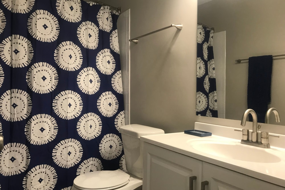 Well-lit bathroom with large vanity mirror in model home at Keystone Farms in Nashville, Tennessee