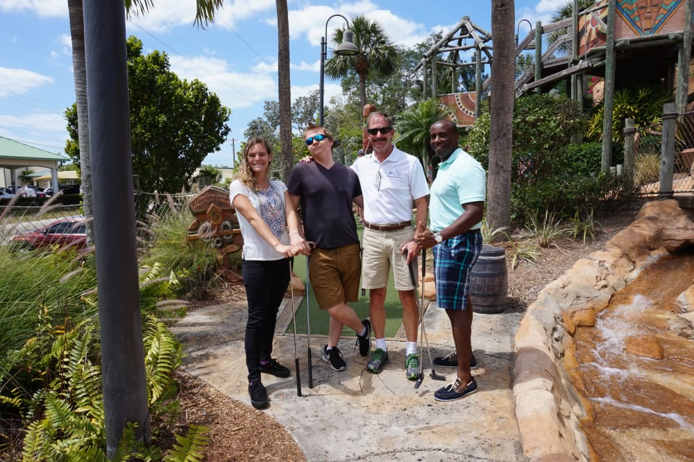 A group of people playing minigolf at Discovery Senior Living in Bonita Springs, Florida