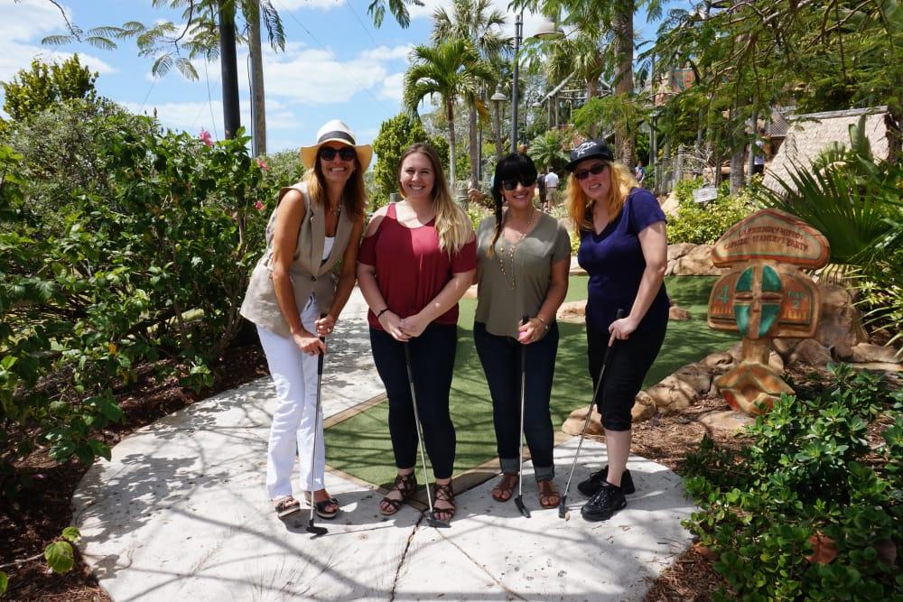 A group posing for the camera at a mini golf course near Discovery Senior Living in Bonita Springs, Florida
