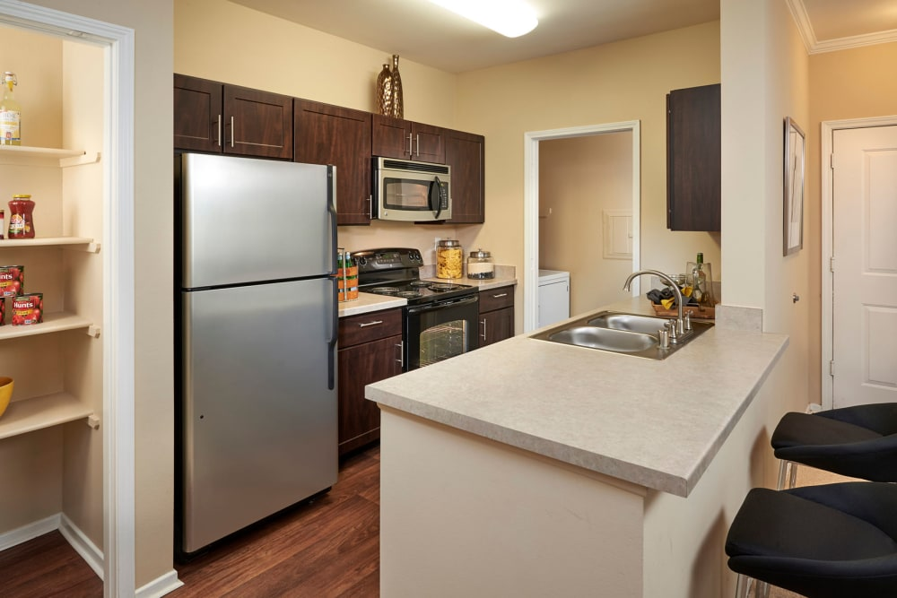 Kitchen with a large breakfast bar at Legend Oaks Apartments in Aurora, Colorado