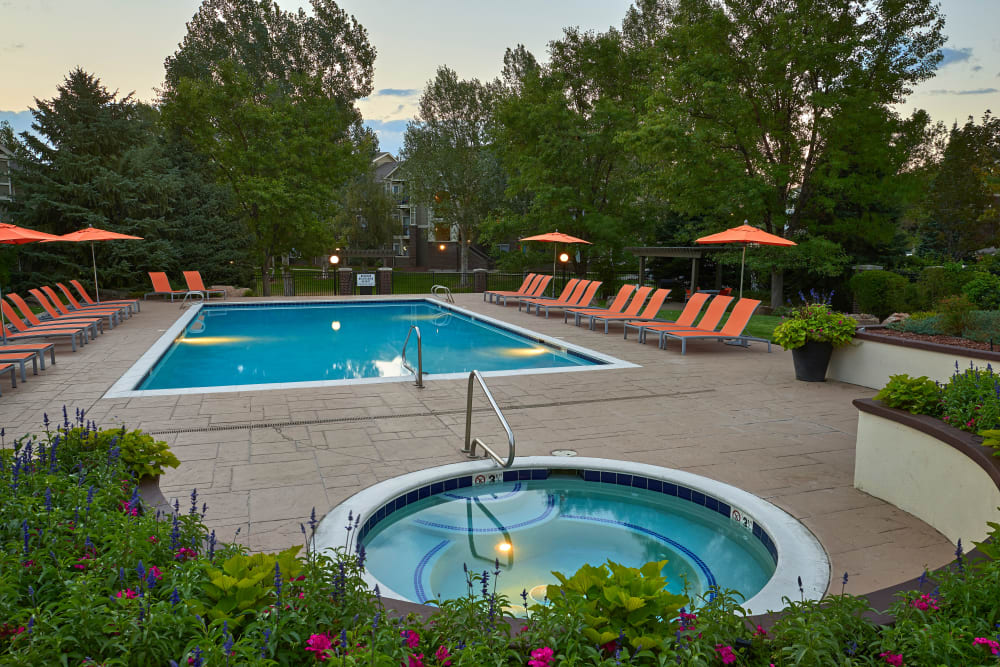 Swimming pool with a sundeck and lounge chairs at Legend Oaks Apartments in Aurora, Colorado
