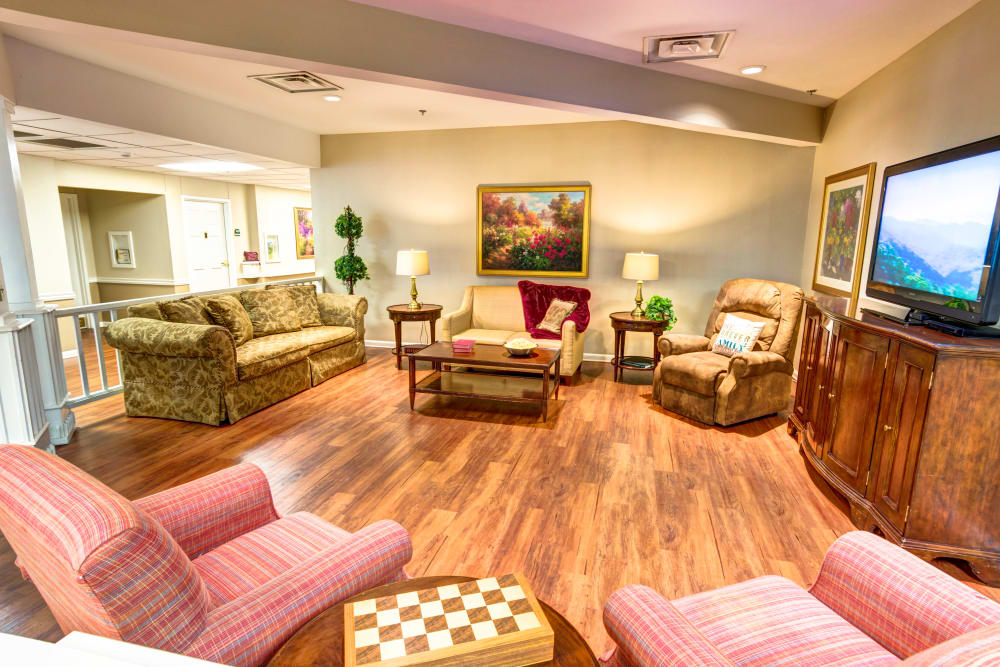 TV room with hardwood flooring and ample seating at Brookstone Assisted Living Community in Fayetteville, Arkansas