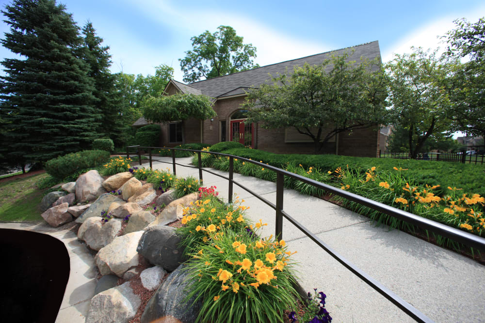 Walkway amid rockery and flowers at Saddle Creek Apartments in Novi, Michigan