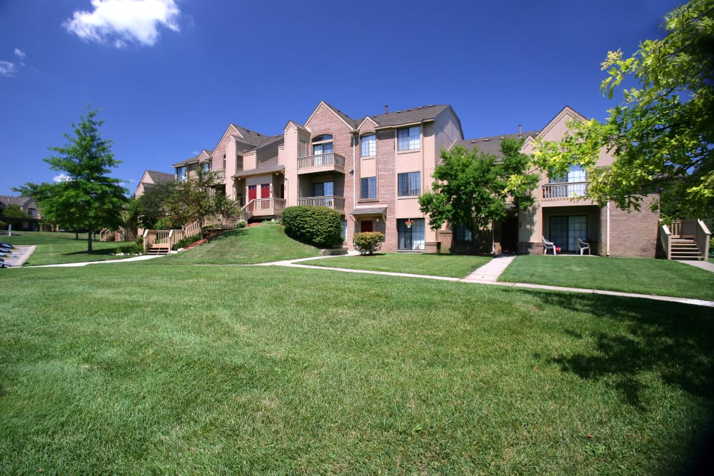 Green grass and resident buildings at Saddle Creek Apartments in Novi, Michigan