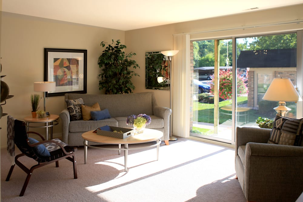 Plenty of natural light in model home's living area at Kensington Manor Apartments in Farmington, Michigan